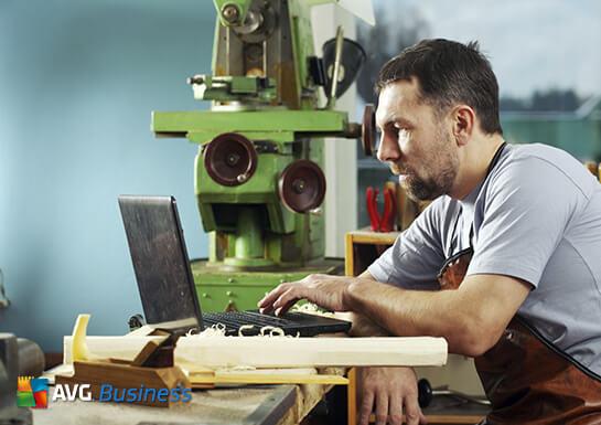 Pria dengan laptop yang menampilkan AVG Business